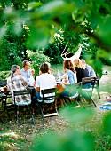 Erwachsene & ein Kleinkind sitzen an gedeckten Gartentisch