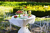 Table in a garden ready laid with strawberry cake, Sweden.