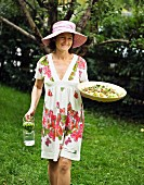 Woman in flowery dress carrying salad and jug of water