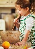 Kleines Mädchen Schokoladenteig abschleckend