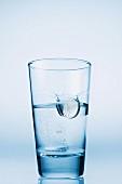 Tablette fällt in ein Glas Wasser