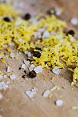 Grated lemon peel, peppercorns and salt crystals on wood
