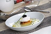 A poached egg with potato cakes on a potato and vegetable cream