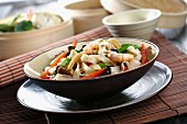 Wide oriental noodles with vegetables and prawns