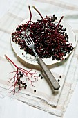 Lots of elderberries, in bunches and individually, on an old plate with a fork