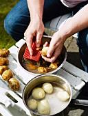 A woman washing potato, Sweden.