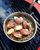 Bonito and potatoes on straw in a pan on a barbecue grate