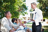 Waiter serving customers in garden
