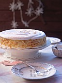 Meringue layer cake with flaked almonds, on a cake stand (for Christmas)