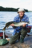 A man holding a pike, Sweden.
