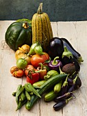A still life of summer vegetables on a wooden table