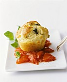 An olive muffin on tomatoes with basil