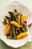 Green asparagus with orange segments and nuts
