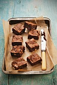 Double chocolate brownies on a baking tray with a knife
