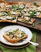 Gemüsepizza mit Rucola, angeschnitten