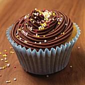 A chocolate cupcake with colourful sugar balls