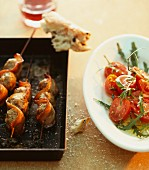 Meatball skewers with bacon, and a tomato and rocket salad