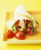 A wrap filled with tomatoes, avocado, parmesan and rocket