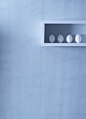 Four white eggs in a shelf on the wall