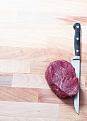 Raw beef fillet steak with a knife