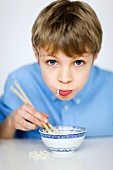 Portrait of boy eating noodles with chopsticks
