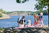 Family preparing for picnic beside lake