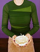A woman holding a bowl of beansprouts