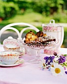 A table outdoors with teacups and cakes in a decorative serving dish