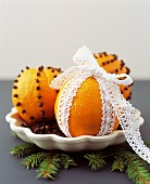 Orange pomanders stuck with cloves and decorated with lace ribbon