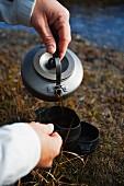 Mann giesst Kaffee in Plastikbecher