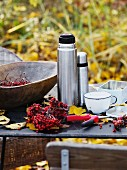 Rowan berries, thermos flasks & cups on table outdoors
