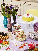 Table set with cake, pastries, flowers & floral cups and crockery