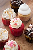Assorted mini cupcakes on a wooden surface