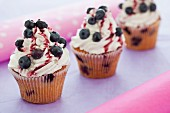 Blueberry cupcakes with mascarpone icing and cherry sauce