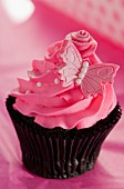 Chocolate cupcake with strawberry icing and a pink butterfly