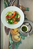Stew with summer vegetables, sausage and pesto