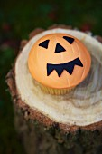 Cupcake decorated with a jack-o'-lantern face for Halloween