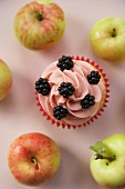 Cupcake with blackberries, surrounded by fresh apples