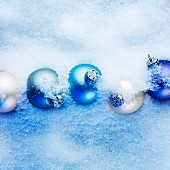 Blue and apricot-coloured Christmas baubles hidden in the snow
