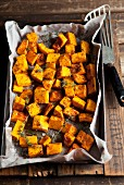 Oven-roasted diced pumpkin with thyme on a baking tray