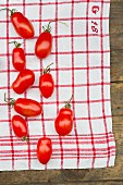 Plum tomatoes on a red & white cloth