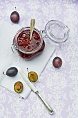 Stewed plums in a jar, with a silver spoon