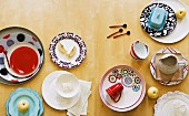 Assorted plates and cups with varying patterns and styles
