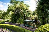 Rustikaler grün lackierter Tisch vor Gartenzaun, teilweise sichtbare formgeschnittenen Hecken in sommerlichem Garten