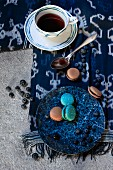 Coffee cup with pattern of blue circles and plate of macaroons on blue and white cloth