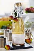 Apfellikör in dekorativer Bügelflasche mit Zieräpfeln, daneben kleine Zinnbecher