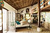 Bett zwischen Fenstertüren in rustikalem Schlafraum mit Dachstütze und Galeriekonstruktion; Abbildungen der Meeresgöttin Lemanja