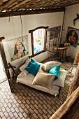 Blick von Galerie auf hellen Ziegelboden und Bett mit türkisen Seidenkissen; an den Wänden Gemälde mit Abbildungen der Meeresgöttin des brasilianischen Candomblés