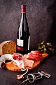 A selection of cold meats with bread, a bottle of red wine and a corkscrew