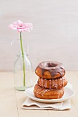 Doughnuts with glacé icing and with chocolate glaze, with a gerbera in the background